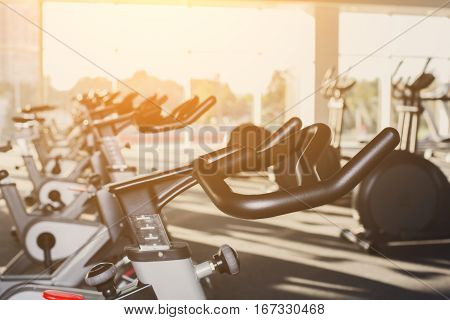 Modern gym interior with equipment. Fitness club with row of training exercise bikes handlebars. Healthy lifestyle concept