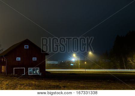 A long exposure of a old farm building at night with farmland in foreground and road with streaks of car lights in the background.