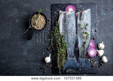 raw sea bass fish cooking on dark background