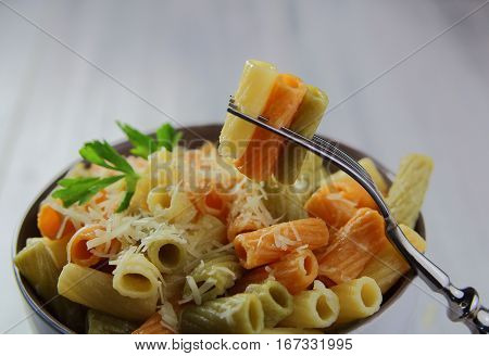 colorful pasta with grated cheese on a fork and dish