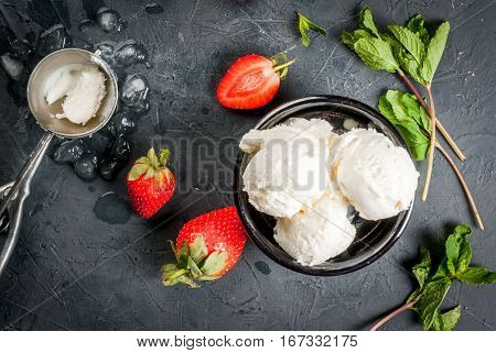 Vanilla ice cream in a classic ice-cream bowls with strawberries and mint ice cream spoon on dark gray stone table top view