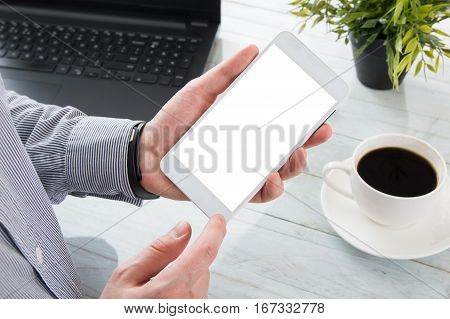 Businessman holds white smartphone with empty screen