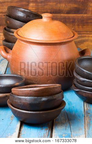 Clay dishes - plates and pot on wooden blue background