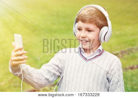 Portrait Of Young Boy With Headphones And Smarphone In The Park
