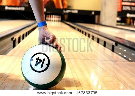 Woman hand holding a bowling ball in hand on bawling alley