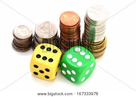 Betting all in concept with ladder of stacked coins and a pair of plastic dice