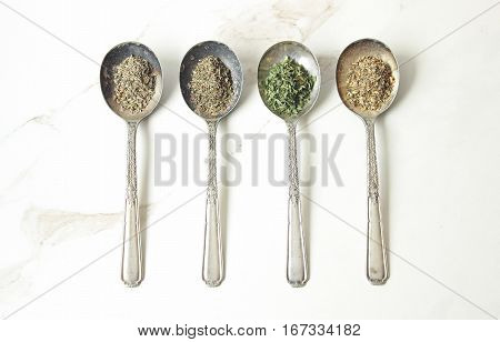 A variety of dried spices on vintage tarnished silver spoons against white marble table top.
