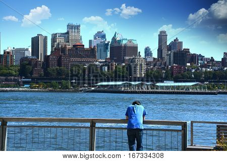 Thoughtful man leaning on railing against Brooklyn, view from Manhattan, New York City