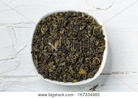 Dried green tea leaves gunpowder in white bowl on white wooden background view from above.