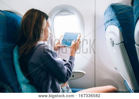 10 years old girl sitting inside airplane and playing on tablet