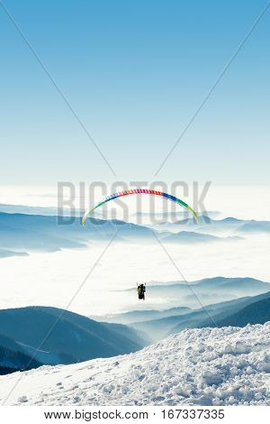 Paraglider in the sky above a snowy mountain
