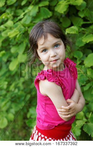 little girl grimacing on a background of green leaves