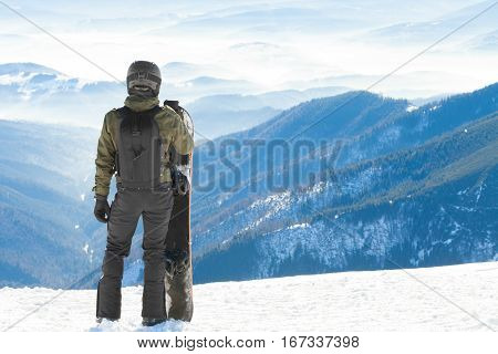 Young Snowboarder Standing Next To Snowboard Thrusted Into Snow And Looking At A Beautiful Mountain