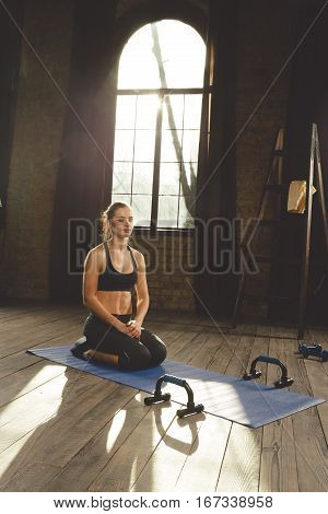 Young athletic woman doing breathing exercises before workout on the mat at home