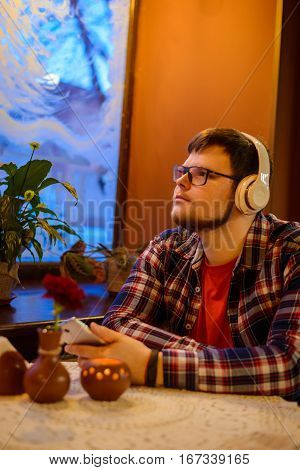 Caucasian man listening to the music while sitting in the cafe witj flower and candel