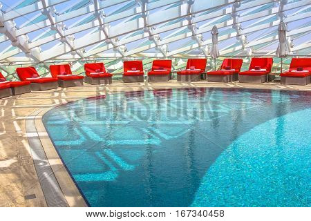 Abu Dhabi, UAE - April 22, 2013: pool and sun loungers in 5-star Resort Hotel Yas Viceroy in Yas Island, built over Yas Marina Circuit of Formula 1. Travel, lifestyle adult and luxury holidays concept