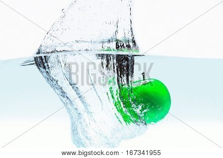Apple falls deeply under water with a big splash. Green apple under water with a trail of transparent bubbles.