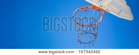 Basketball hoop and backboard form behind with wide view and sky background.