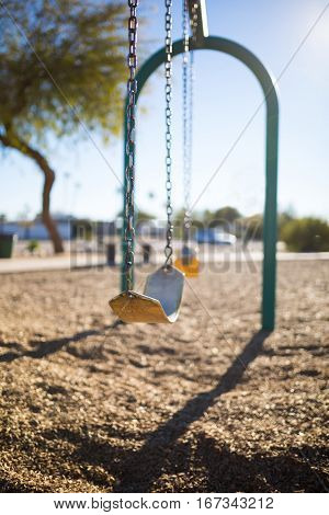 Play park kid's swings in a row. Depth of field view and close up of first swing/harness. poster