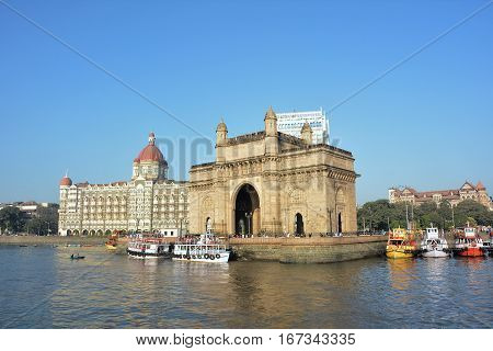 MUMBAI INDIA - JANUARY 11 2017: Taj Mahal Palace Hotel and Gateway of India. Both structures in Mumbai Harbor overlook the Arabian Sea.