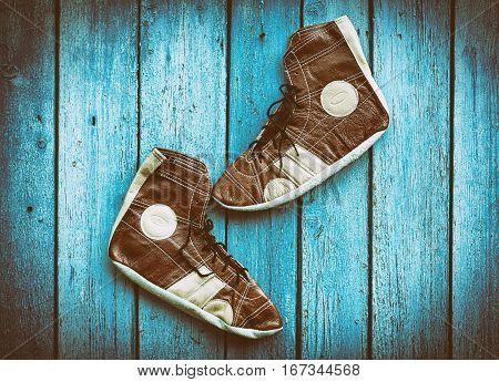 Vintage leather shoes for wrestling blue wood background vintage toning