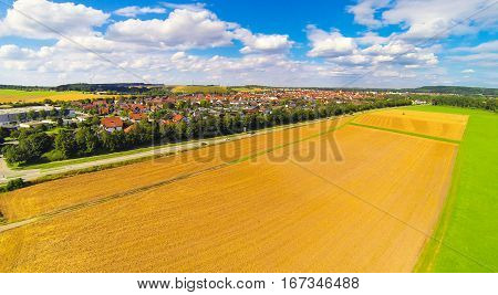 aerial view of small german town with harvested fields in the foreground