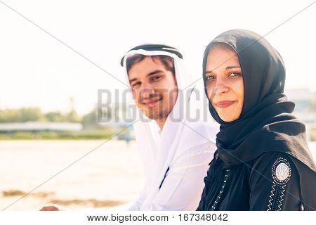 arabian couple sitting on jumeirah beach in dubai
