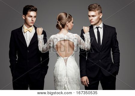 Two handsome men in suits and beautiful woman in white bridal dress. Studio, trendy, strict look