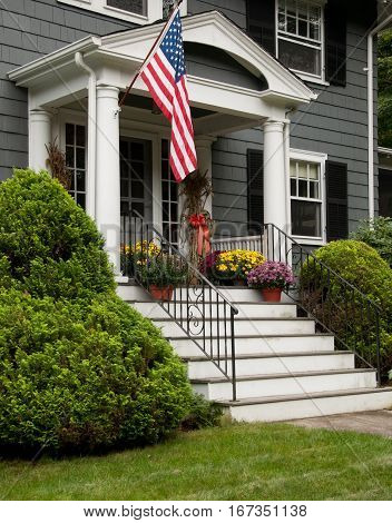 Grey House with U S Flag and steps and flowers