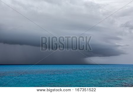 A severe thunderstorm over the ocean off the coast of Bermuda. The anvil shaped cumulonimbus incus clouds are seen with rain falling.