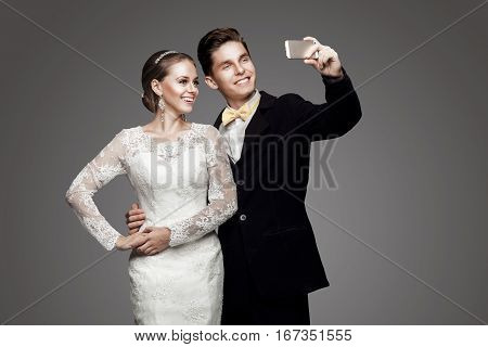 Groom in black suit and yellow bow-tie with bride in wedding dress taking a selfie.
