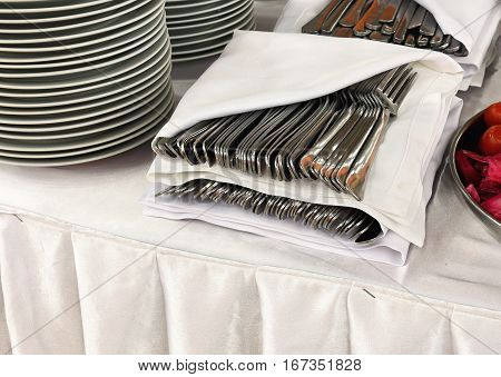 Forks and spoons in a white envelope on the buffet table