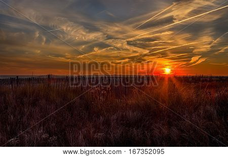 A sunset over the ocean at the beach shore in Cape May New Jersey.