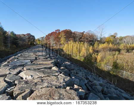Hurricane barrier bordered by trees in fall foliage in Fairhaven Massachusetts