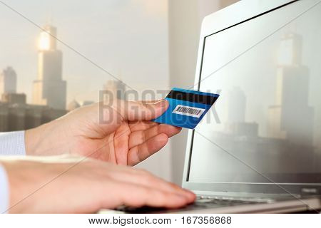 business man entering data of a credit card . On-line shopping on the internet using a laptop
