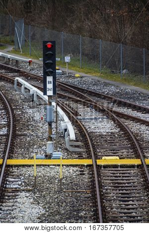 Rail tracks in Froettmaning (Munich) with a red traffic light