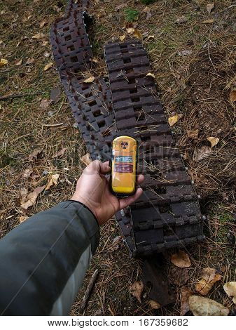 Dosimeter showing higher radiation in front of an old tank track in the Chernobyl Exclusion Zone which was established after the nuclear disaster in 1986
