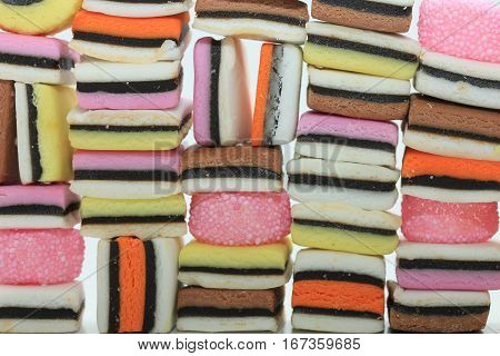 Stacked liquorice allsorts in different shapes colors and sizes