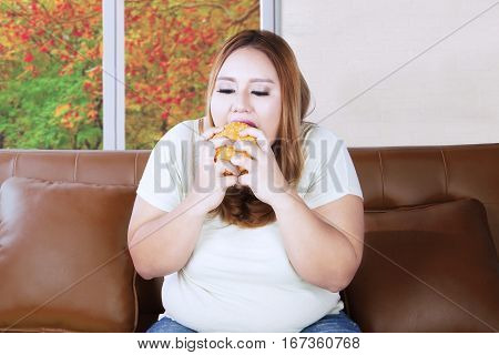Image of fat woman starving and eating hamburger while sitting on the couch with autumn background on the window