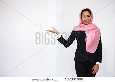 Empty hand holding of smiling businesswoman in black suit wearing pink turban on white background.