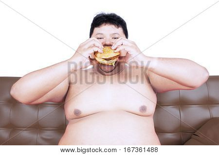 Image of greedy fat man sitting on the brown sofa while eating delicious hamburger in the studio