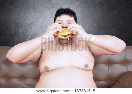 Image of greedy fat man sitting on the brown sofa while eating delicious hamburger