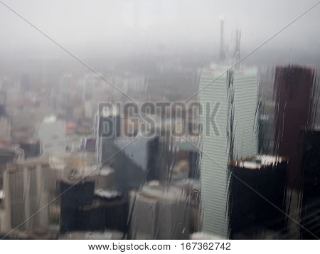 A gloomy fiew of downtown Toronto Canada through a glass window on a rainy day.