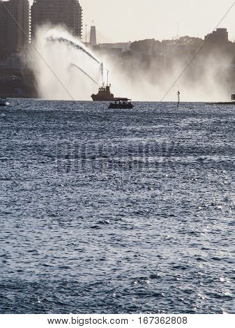 Firefighter boat spraying water in Sydney harbor.