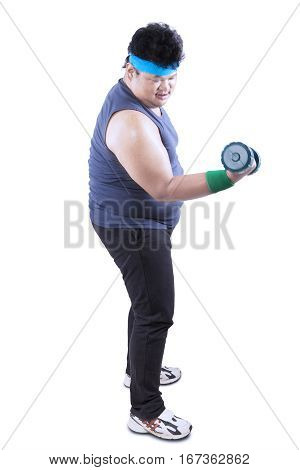 Full length of obese young man standing in the studio while exercising with dumbbells