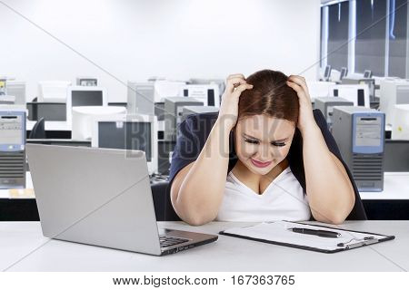 Portrait of stressful woman holds her head while sitting in front of her laptop in the office