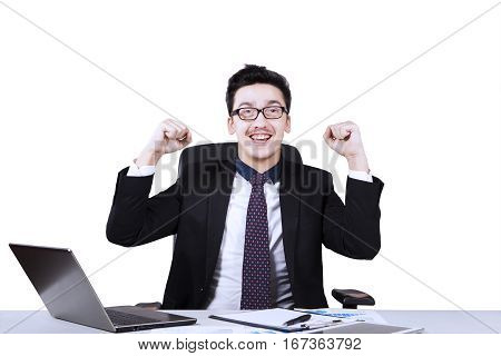 Arabian businessman raising hands and sitting in the studio while working with laptop and paperwork on the desk