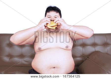 Voracious obese man eating yummy hamburger while sitting on the brown couch with shirtless in the studio