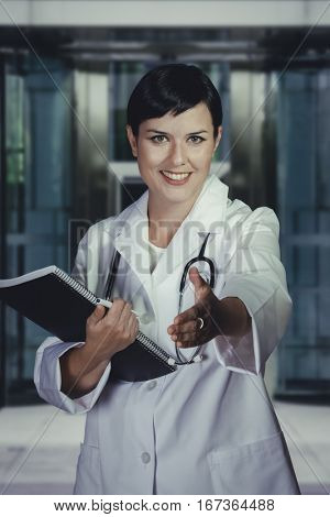Smiling medical doctor with stethoscope. Over hospital background