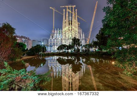Barcelona, Spain - November 24, 2016: La Sagrada Familia illuminated at night reflecting in the water. The cathedral was designed by Antoni Gaudi and has been under construction since 1882 in Barcelona Spain.